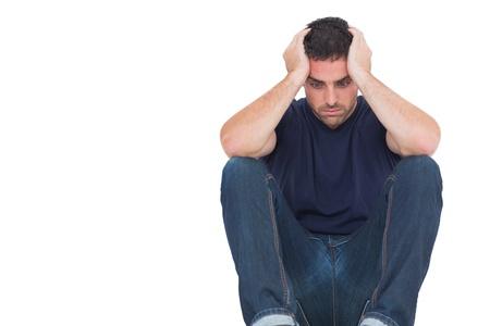 sad man: Hombre triste que se sienta en el suelo mientras sostiene la cabeza en el fondo blanco Foto de archivo