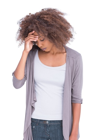 Sad woman holding her forehead on white background