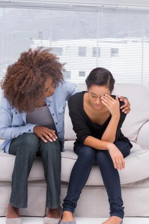Mujer llorando junto a su terapeuta que está consolando