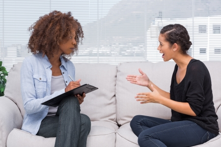 Upset woman speaking to her therapist while she is taking notes photo
