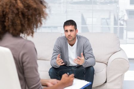 Depressed man speaking to a therapist while she is taking notes photo