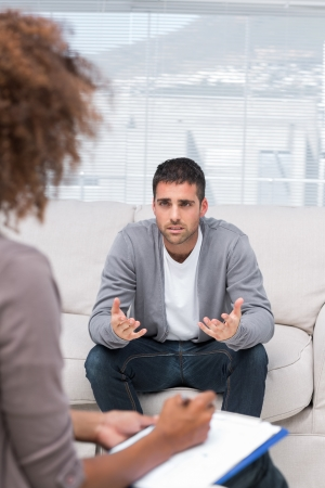 mental health: Man speaking to a therapist while she is taking notes Stock Photo