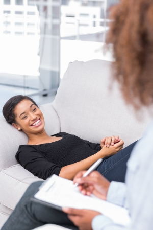 counseling: Woman laughing on sofa during therapy session with therapist taking notes Stock Photo