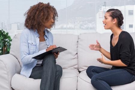 Vrouw gebaren en spreken tot haar therapeut, die is het maken van aantekeningen