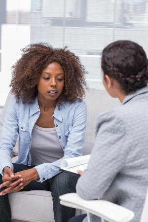 Patient sitting on sofa and talking to therapist during therapy Imagens
