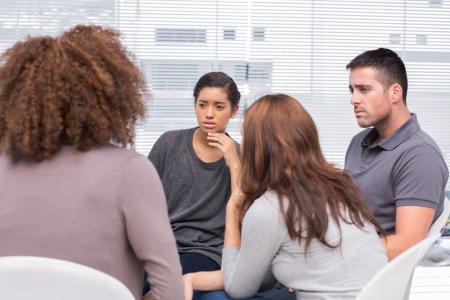 support group: Patients listening to another patient during therapy session Stock Photo
