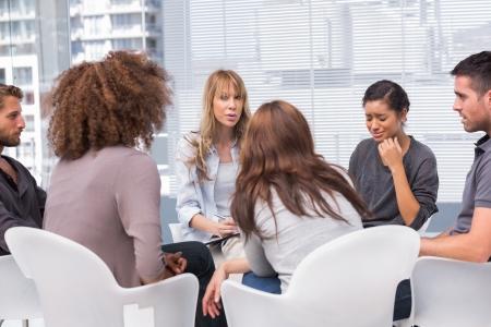 terapia grupal: Mujer llorando durante la sesión de terapia con otras personas y terapeuta Foto de archivo