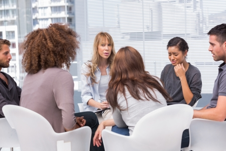 Woman crying during therapy session with other people and therapist photo