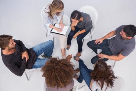 terapia de grupo: Terapeuta escuchar el paciente durante la sesi�n de terapia de grupo Foto de archivo