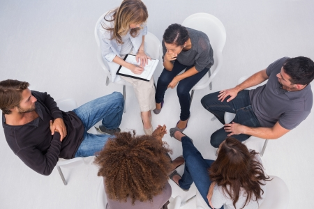 Therapist listening to patient during group therapy session photo