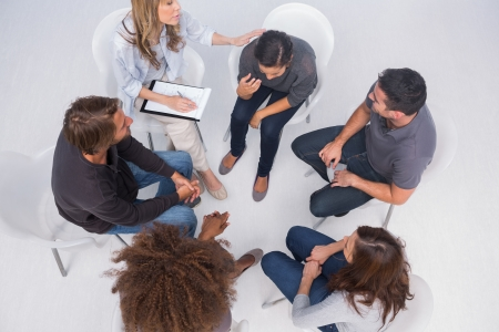 support group: Therapist comforting her patient crying during group therapy Stock Photo