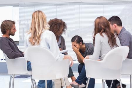 terapia de grupo: Terapeuta escuchar a una mujer llorando durante la terapia de grupo