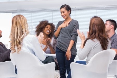 Smiling patient standing and telling her problems during therapy group session photo