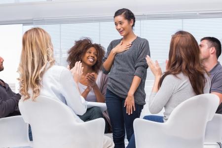 terapia de grupo: Sonriendo paciente de pie y diciendo a sus problemas durante la sesión de terapia de grupo
