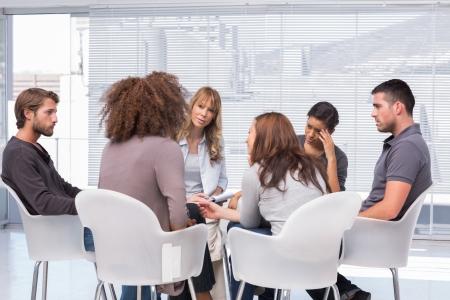 グループ療法のセッションでその問題を伝えるセラピスト中の患者