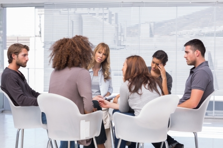 support group: Patients around therapist telling their problems in group therapy session Stock Photo