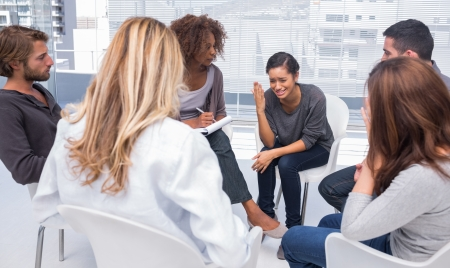Woman sitting on chair and getting depressed in group therapy Stock Photo