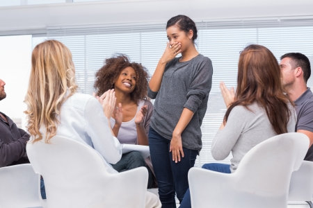 mental health: Happy patient standing and feeling overwhelmed while other patients are clapping