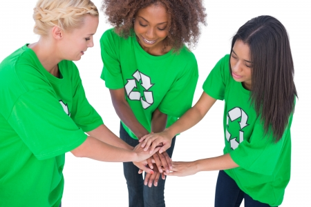 activists: Three enviromental activists putting their hands together on white background Stock Photo