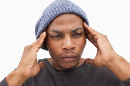 desolaci�n: Hombre preocupante de la gorrita tejida del sombrero en el fondo blanco