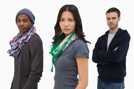 unsmiling: Serious stylish young people in a row on white background