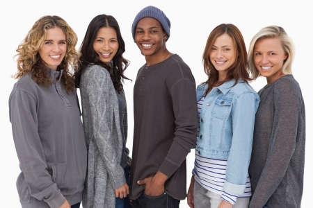 Fashionable young people in a row smiling on white background photo