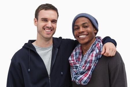 casual hooded top: Dos amigos de moda mirando a la c�mara y sonriendo sobre fondo blanco Foto de archivo