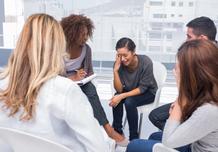 psychiatry: Woman getting distressed in group therapy with other patient listening