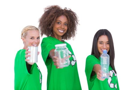 enviromental: Three smiling enviromental showing recyclable matierials on white background