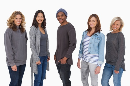 Fashionable young people in a line smiling on white background photo