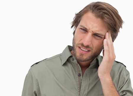 wincing: Man with headache looking away and wincing on white background