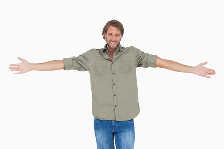 arm outstretched: Smiling man with arms open wide on white background Stock Photo