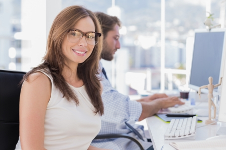 Pretty designer smiling at camera as colleague works behind her photo