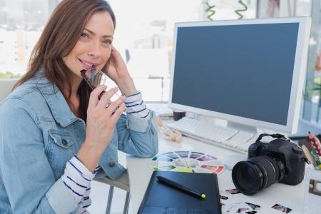 Photo editor pensieroso alla sua scrivania con la tavoletta grafica e la macchina fotografica