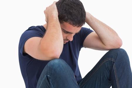 desolaci�n: Infeliz con la cabeza en las manos sentado en el suelo en el fondo blanco