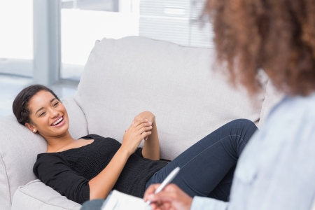 counseling: Woman lying on therapists couch looking happy as therapist is writing