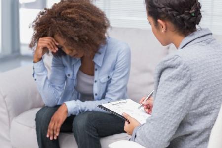 メモを取ってセラピストで見下ろしているセラピストのソファの上に座っている女性