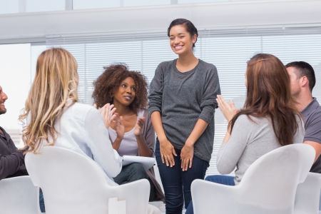 counseling: Patient has a breakthrough in group therapy and everyone is clapping her Stock Photo