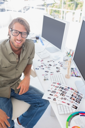 Photo editor looking up from his work and smiling in bright modern office Stock Photo - 20516906