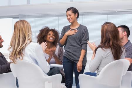 terapia de grupo: Feliz paciente tiene un gran avance en la terapia de grupo, mientras que otros est�n aplaudiendo su Foto de archivo