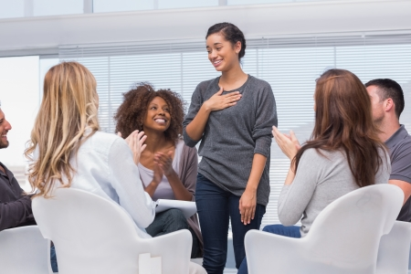 multiracial groups: Happy patient has a breakthrough in group therapy while others are clapping her