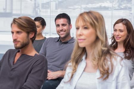 terapia de grupo: Los pacientes que escucha en la terapia de grupo con un hombre que sonr�e en la c�mara en la Oficina