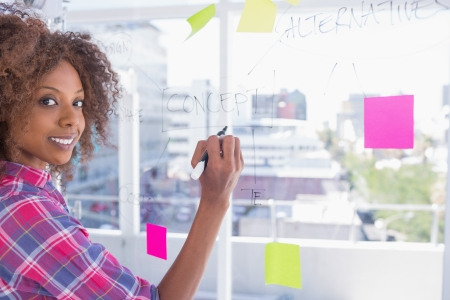 Woman drawing on flowchart with marker and smiling at camera in bright office photo
