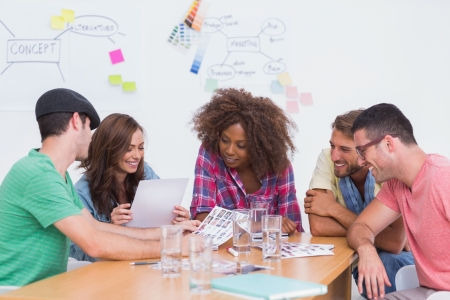 Creative team going over contact sheets in meeting in office with whiteboard Stock Photo