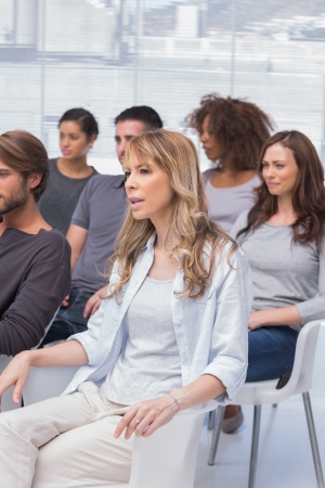 Patients listening in a therapy session sitting on chairs photo