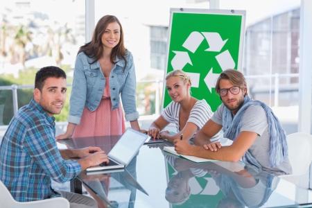 comité d entreprise: L'équipe ayant réunion sur le recyclage et souriant à la caméra dans le bureau lumineux