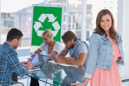 comité d entreprise: L'équipe ayant réunion sur le recyclage politique avec une femme debout et souriant à la caméra
