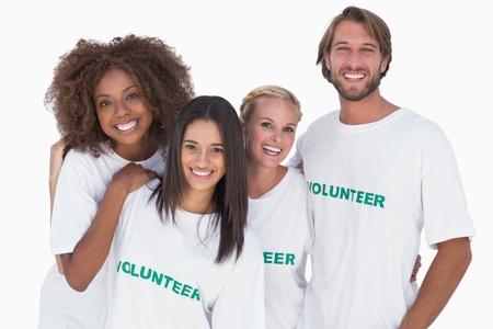 altruismo: Grupo de voluntarios sonrientes en el fondo blanco Foto de archivo