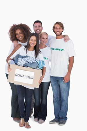altruismo: Feliz grupo de voluntarios con caja de donaci�n en el fondo blanco Foto de archivo