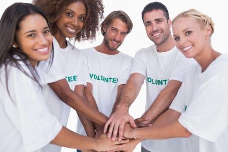 白い背景の上に手を一緒に入れてボランティア グループの笑みを浮かべてください。